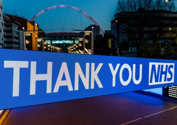 Wembley Parks Bobby Moore Bridge illuminated with a Thank You NHS sign